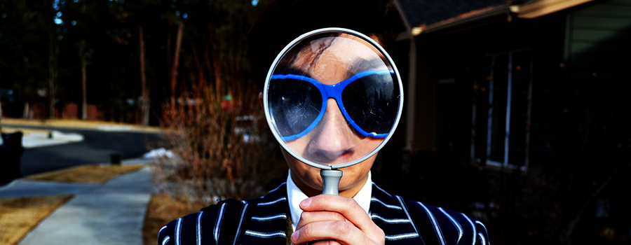 Man looking through a large magnifying glass. SEO for dispensary marketing. SEO for medical marijuana companies. Medical marijuana marketing strategy and ideas. 420Digital.ca - Cannabis marketing agency Canada and USA.