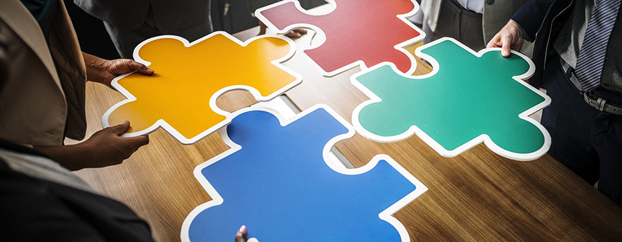 4 large puzzle pieces being brought together by 4 cannabis business owners. Cannabis marketing agency Canada and USA. Dispensary marketing strategy. Cola Digital Cannabis Marketing. ColaDigital.ca.