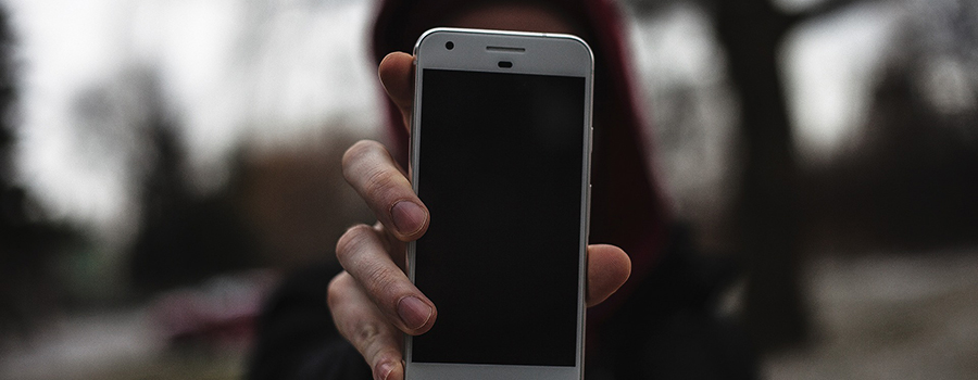 Woman holding a cellphone to the camera. How to promote your dispensary on Facebook. Dispensary marketing tips. Dispensary marketing agency Cola Digital.