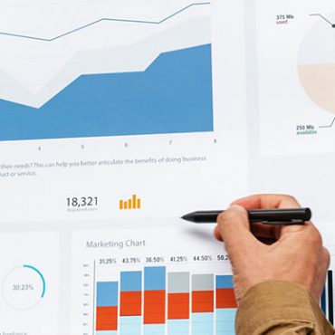Hand with a pen looking at graphs and charts showing cannabis SEO data. Marijuana SEO tips. Cannabis marketing agency. Cannabis SEO agency USA and Canada.