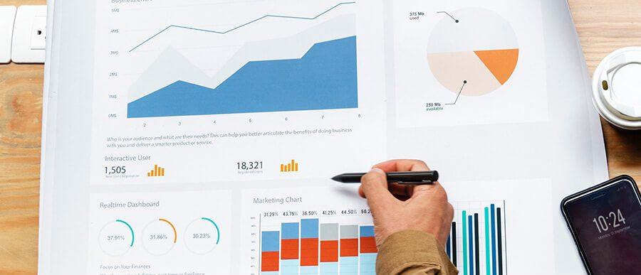 Hand with a pen looking at graphs and charts showing cannabis SEO data. Marijuana SEO tips. Cannabis marketing agency. Cannabis SEO agency USA and Canada.