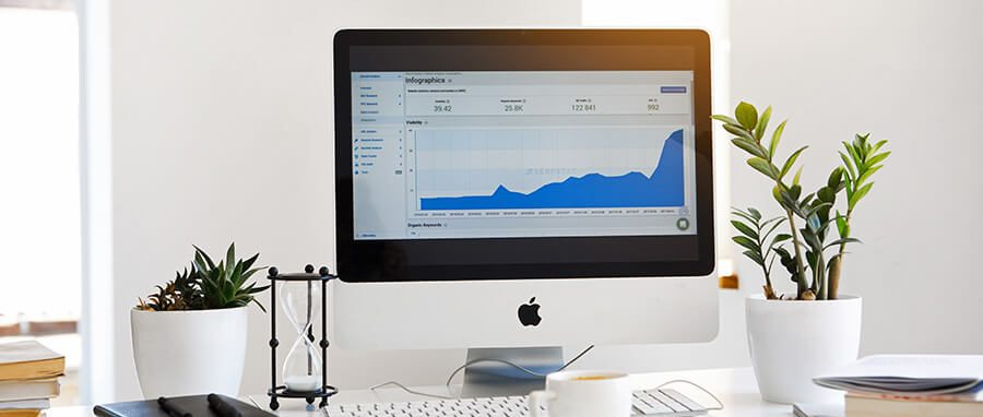 Desktop with large Apple monitor, keyboard, and coffee mug. Dispensary marketing strategy. Marketing ideas for Marijuana Dispensaries.