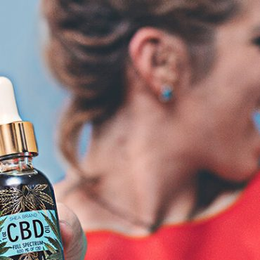 Woman holding out CBD oil with a stretched hand and smiling. How to market CBD products on Google and Facebook. How to promote CBD products on Facebook. Advertise CDB on Google PPC.