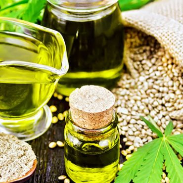 CBD oil in vials with hemp seeds and marijuana leaves. How to market CBD oil products online. CBD Marketing Tips from CBD marketing agency ColaDigital.ca.
