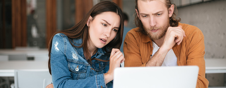 Adult couple searching for cannabis information on a laptop. CBD SEO marketing agency.