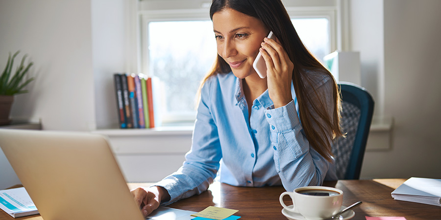 woman on phone behind laptop online shopping. cbd seo agency coladigital.ca.