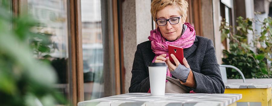 adult woman with coffee and smartphone. marijuana seo agency. dispensary marketing company.
