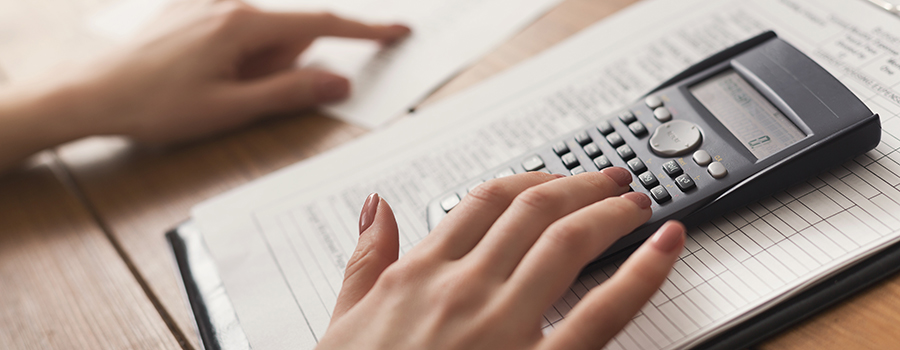 closeup of woman hands counting on calculator. how to market CBD products on line. CBD advertising agency.
