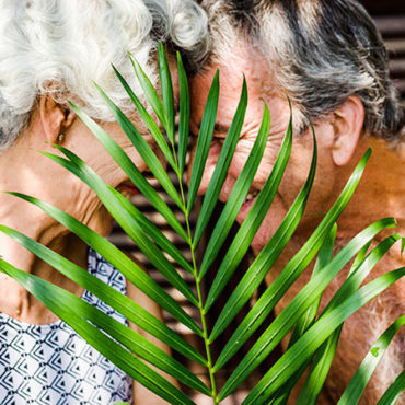 mature couple hiding behind large leaf. how to market a cannabis dispensary.