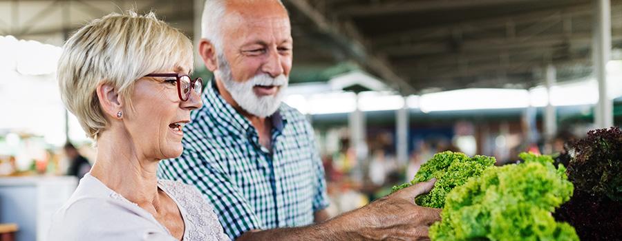 mature couple shopping vegetables and fruits. marijuana seo company.