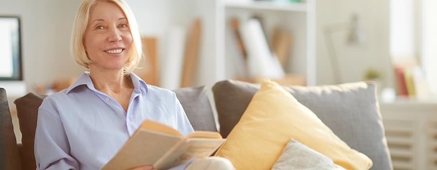 smiling adult woman reading book. marijuana marketing strategies. cannabis seo agency.