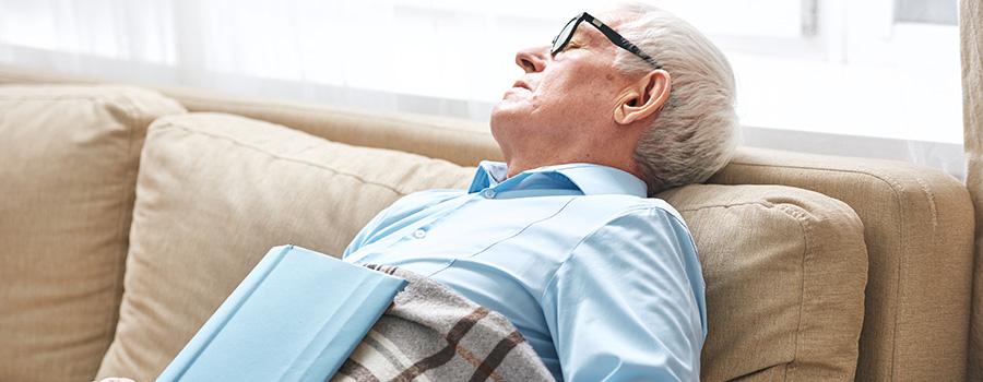 tired senior man napping on couch. marijuana seo agency.