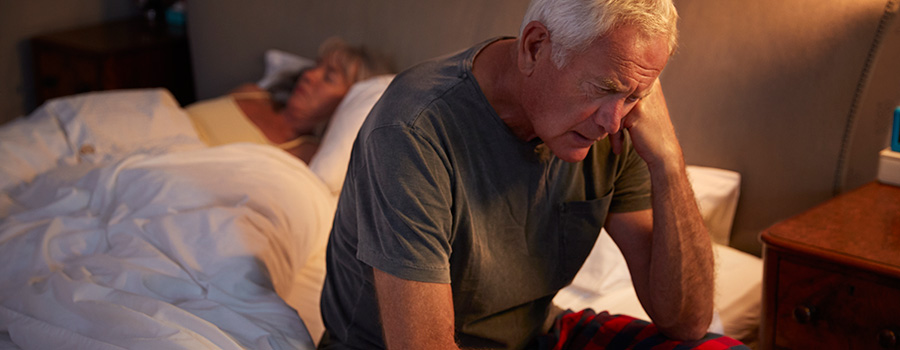 worried senior man in bed at night wishing he had marijuana to smoke. dispensary marketing ideas USA and Canada.